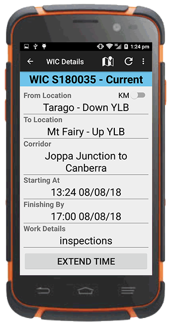 Track worker using ETW application on tablet beside railway track, near track vehicle